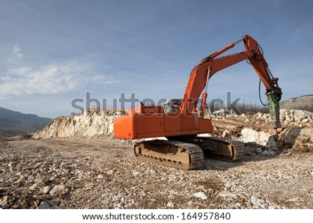 Orange backhoe drilling stone soil on construction of road - stock photo