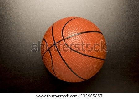 Orange ball  on a dark surface/ Basketball/Sports equipment for competition and recreation.