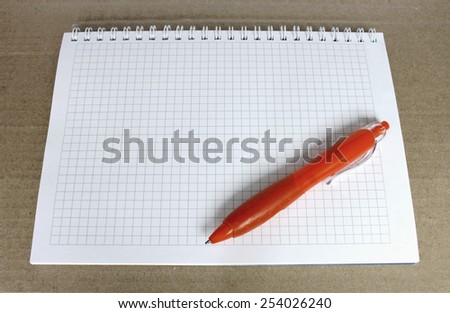 Orange ballpoint pen on the Notepad with a blank page in the box. Notepad on rough brown paper. - stock photo