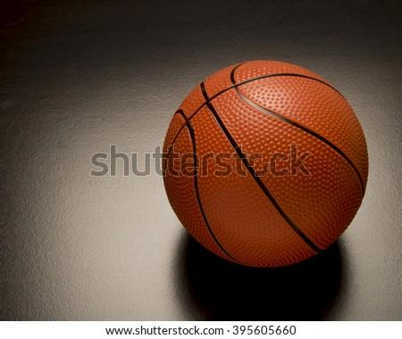 Orange basketball  on white surface/Orange Basketball/Orange basketball for competition and recreation. - stock photo