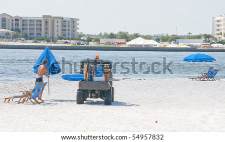 ORANGE BEACH, AL - JUNE 10:  A beach chair vendor removes his umbrella on a beautiful day at Perdido Pass, AL on June 10, 2010 as the BP oil washing ashore drives away customers. - stock photo