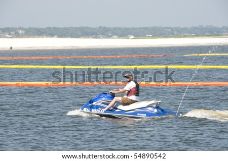 ORANGE BEACH, AL- JUNE 8: A recreational boater motors past protective oil boom positioned in Perdido Pass on June 8, 2010 in an effort to protect Orange Beach, AL from the BP oil spill. - stock photo