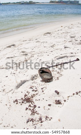 ORANGE BEACH, AL - JUNE 10: An oil soaked flip flop next to a large area of thick black oil splotches at Perdido Pass on June 10, 2010 as the BP oil spill washes ashore. - stock photo