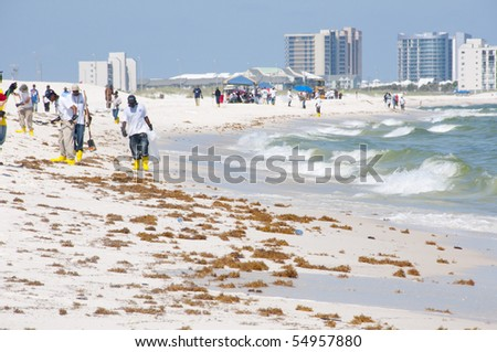 ORANGE BEACH, AL - JUNE 10: BP oil spill workers attempt to remove thick globs of oil from the seashore of Perdido Pass, AL on June 10, 2010 as oil washes ashore in the resort area. - stock photo