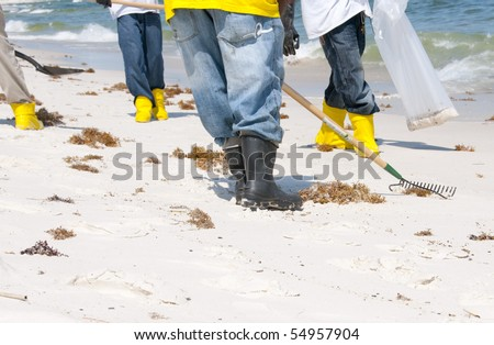 ORANGE BEACH, AL - JUNE 10: BP oil spill workers wearing rubber boots attempt to remove thick globs of oil from the seashore of Perdido Pass, AL on June 10, 2010 as oil washes ashore in the resort area.
