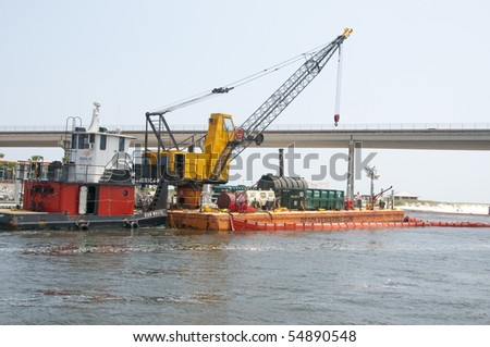 ORANGE BEACH, AL - JUNE 8: Cranes are positioned above oil booms being placed in Perdido Pass on June 8, 2010 in an attempt to protect Orange Beach, AL from the oil slick. - stock photo