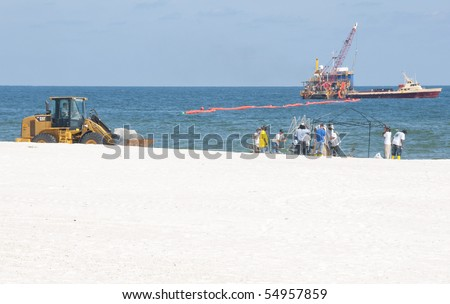 ORANGE BEACH, AL - JUNE 10:  Oil spill workers attempt to clean up oil froma  beach in a tourist resort area on June 10, 2010 in Orange Beach, AL. The beaches are empty except for workers in the height of the tourism season. - stock photo