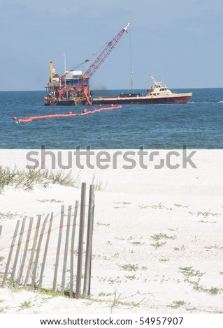 ORANGE BEACH, AL - JUNE 10:  Oil spill workers clean up the wash-ashored oil as the beaches in the tourist resort Orange Beach, AL are empty in the height of the tourism season on June 10, 2010. - stock photo