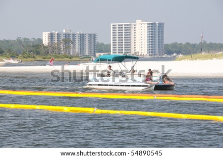 ORANGE BEACH, AL - JUNE 8: Recreational boaters navigate through oil boom draped in Perdido Pass on June 8, 2010 in an effort to protect the Orange Beach, AL resort area. - stock photo