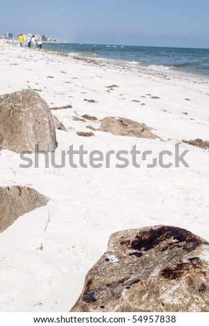 ORANGE BEACH, AL - JUNE 10:  Thick oil has settled onto huge boulders at Perdido Pass, AL on June 10, 2010 as workers try to remove oil now present on the beach (background). - stock photo