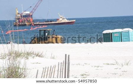 ORANGE BEACH, AL - JUNE 10: Tractors deliver portable toilets to service oil spill workers at Perdido Pass, AL on June 10, 2010 as oil washes ashore as oil containment efforts continue (background). - stock photo