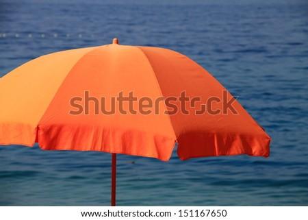 Orange beach umbrella with Adriatic sea in background - stock photo