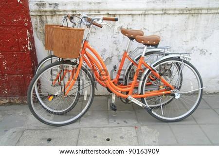 orange bicycle park near wall - stock photo