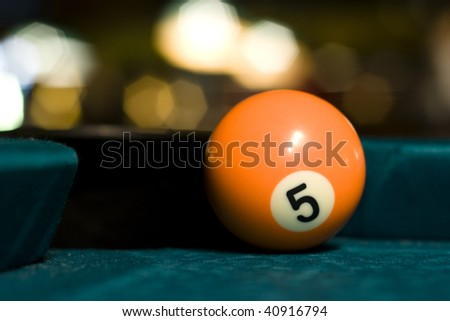 Orange billiard ball on a pool table at the corner pocket