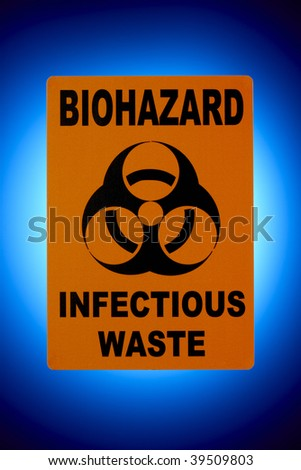 Orange biohazard sign shot in front of glowing blue background - stock photo