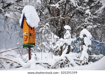 orange birdhouse covered with snow