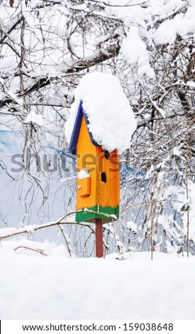 orange birdhouse in winter covered with snow - stock photo