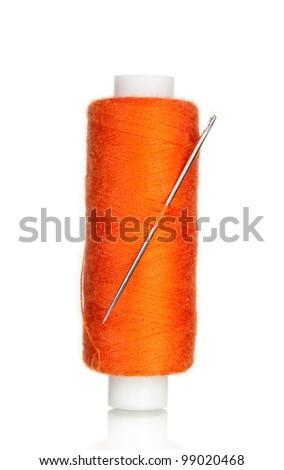 orange bobbin thread with needle isolated on white - stock photo