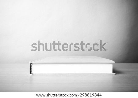 orange book on wood table background black and white color tone style