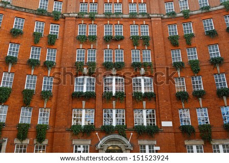 Orange brick building with plants in windows