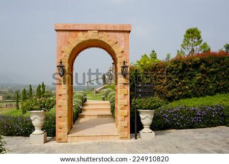 Orange brick wall into garden - stock photo