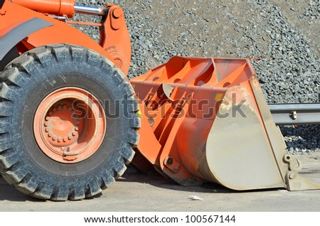 Orange bulldozer on bridge road construction site - stock photo