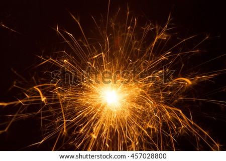 Orange burst of a sparkler in long exposure close up   - stock photo