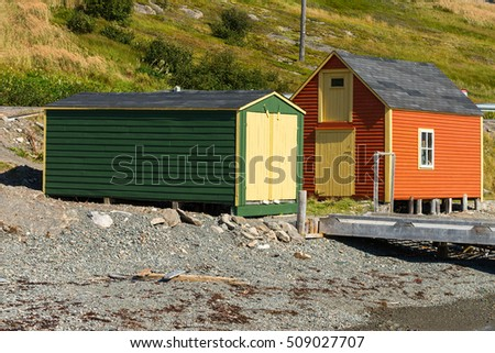 Orange cabin and a green shed