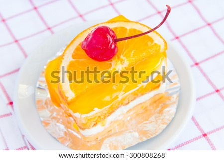 Orange cake with a cherry red delicious and palatable.