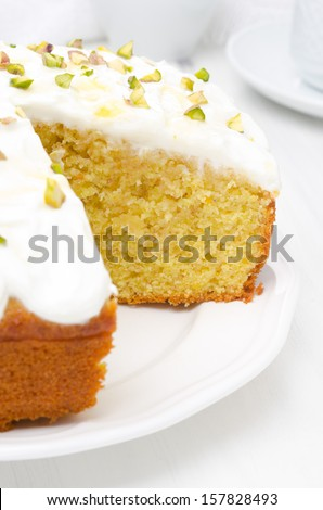 orange cake with Greek yogurt, honey and pistachios in a cut, close-up, vertical