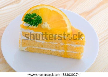 orange cake with orange topping in wooden dish