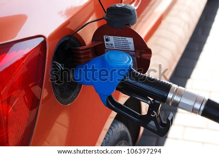 orange car at gas station - stock photo