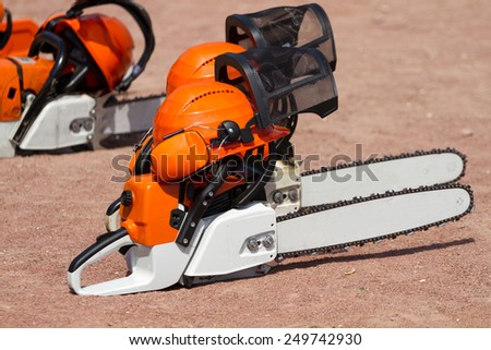 Orange chainsaw and helmets on the ground - stock photo