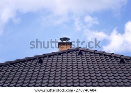 Orange chimney on tiled roof - stock photo