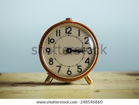 Orange clock on a yellow table against a blue backdrop - stock photo