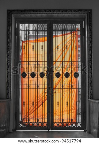 Orange Cloth of Monk hang with door of temple for dry in the sun. - stock photo