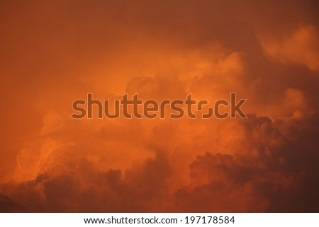 Orange Clouds. Closeup view of a billowing cloud formation illuminated by the setting sun. Shot is graduated diagonally top left to bottom right light orange to darker brown - stock photo