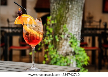 orange cocktail drink in front of a green tree - stock photo