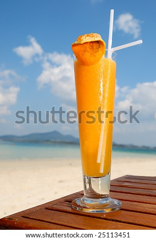 Orange cocktail in beach setting - stock photo