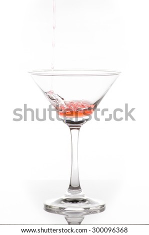 orange cocktail in glass isolated on white background, orange water flows into the glass and makes bubbles isolate on white background