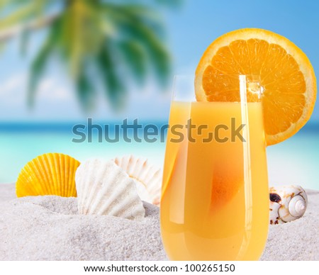 Orange cocktail on a beach - stock photo