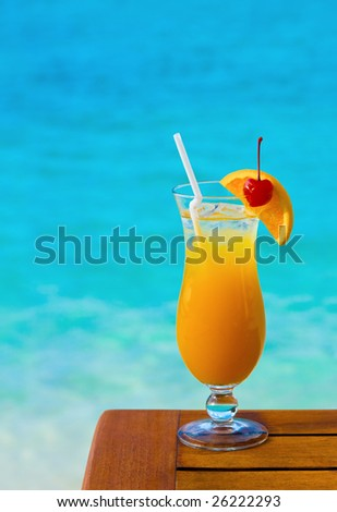 Orange cocktail on table, sea background - stock photo