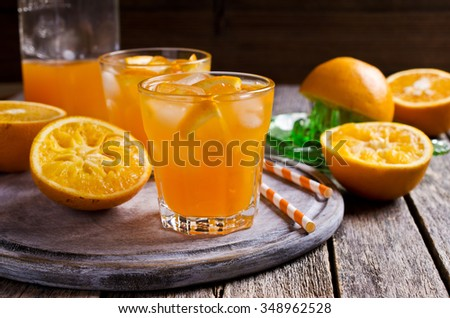 Orange cocktail with ice in a glass on a wooden surface. Selective focus. - stock photo
