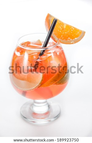 orange cocktail with lime in a hurricane glass - stock photo