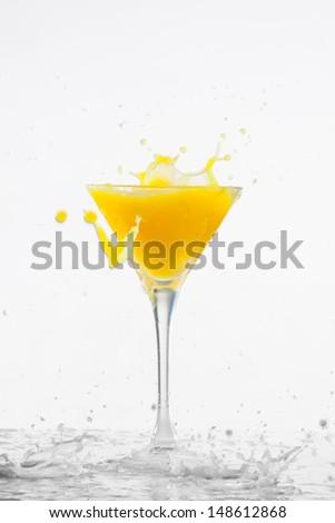 Orange cocktail with splashes on a white background - stock photo