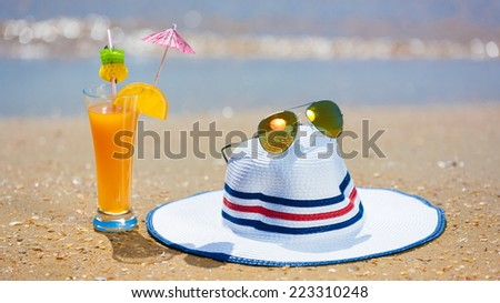 orange cocktail with white hat and yellow sunglasses on the beach