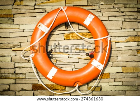 Orange color of Ring buoy on the stonewall at the beach prepare for emergency case - stock photo
