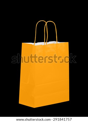 Orange colour paper carrier bag, isolated on black. Halloween shopping maybe.