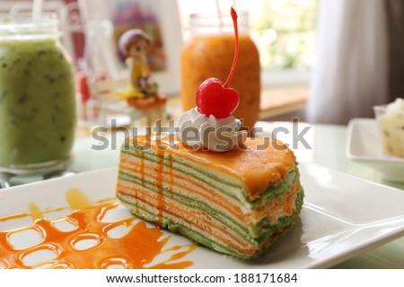 Orange crepe cake and orange jam topping with cherry  - stock photo