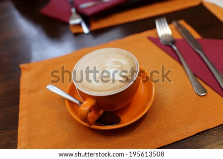 Orange cup of coffe in the cafe - stock photo